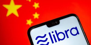 A visual representation of Facebook Libra logo on a smartphone resting on a Chinese logo background